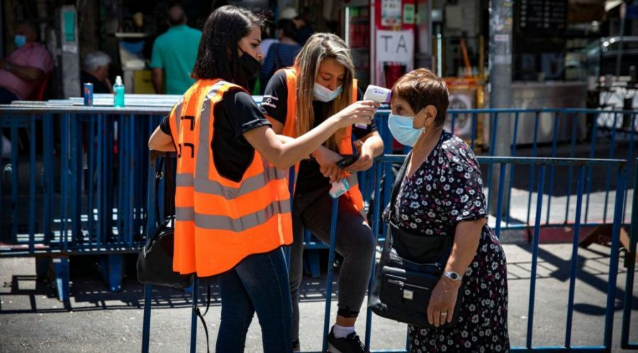 An+Israeli+woman+has+her+temperature+taken+before+entering+the+Mahane+Yehuda+market+in+Israel%2C+part+of+a+national+effort+to+halt+the+spread+of+the+coronavirus%2C+June+16%2C+2020.+%28Olivier+Fitoussi%2FFlash90%29