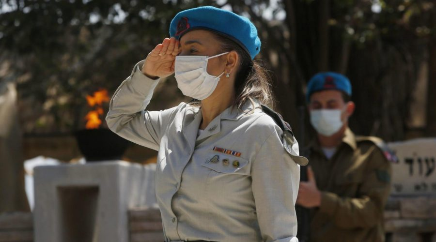 Israeli soldiers, wearing mandatory protective masks due to the COVID-19 coronavirus pandemic, pay tribute to fallen soldiers at the Kiryat Shemona military cemetery in northern Israel, April 28, 2020. (Jalaa Marey/AFP via Getty Images)