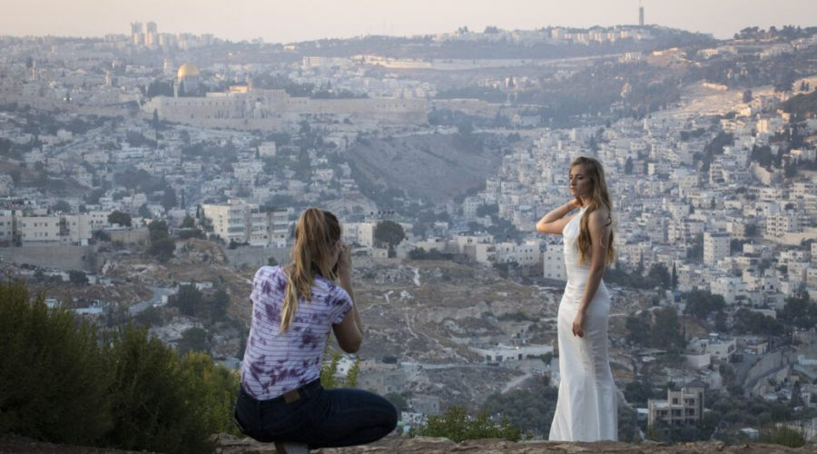 In+a+photo+from+August+2019%2C+an+Israeli+woman+in+a+wedding+dress+is+photographed+a+few+days+before+her+wedding+with+a+view+of+the+Old+City+of+Jerusalem+in+the+background.+%28Hadas+Parush%2FFlash90%29%C2%A0
