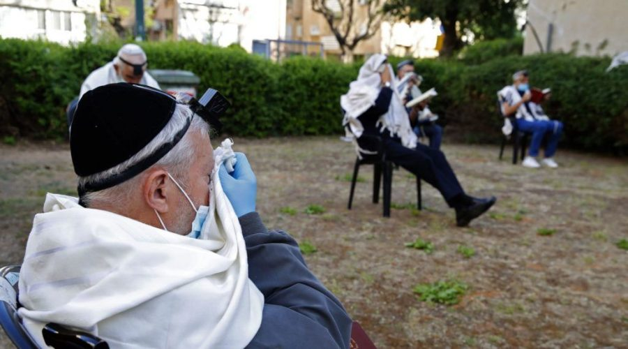 Jewish men pray while keeping distance from each other outside their closed synagogue in Netanya, Israel, April 23, 2020. (Jack Guez/AFP via Getty Images)