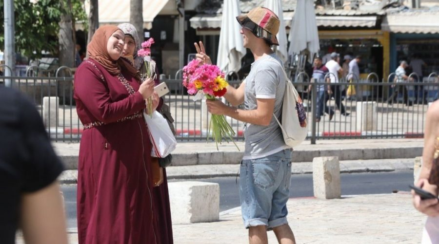 An activist with Tag Meir, an Israeli group funded by the New Israel Fund, hands out flowers on a day to counter racism in Jerusalem on June 1, 2019. (NIF/Yossi Zamir)