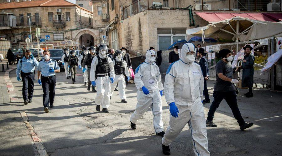 Israeli police officers wearing protective clothing as a preventive measure against the coronavirus in the religious neighborhood of Meah Shearim, April 6, 2020. (Yonatan Sindel/Flash90)