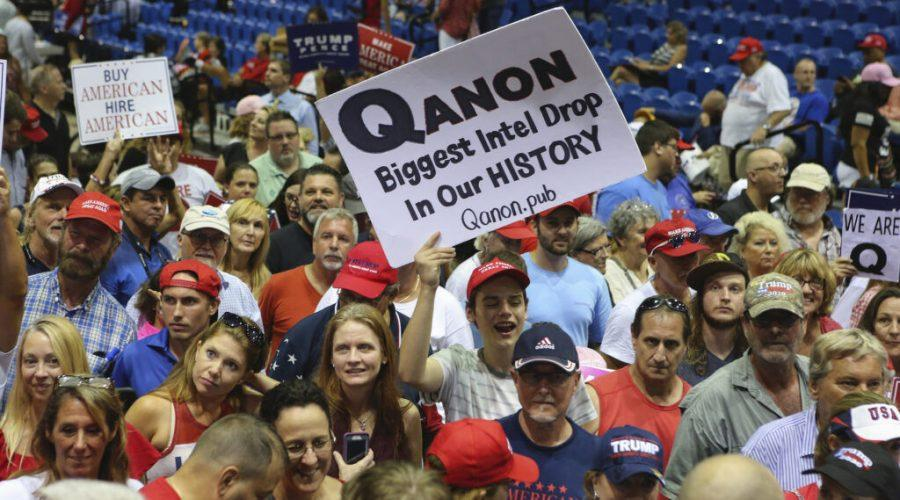 Trump+supporters+display+QAnon+posters+at+a+2018+rally+in+Florida.+Recently%2C+Latinos+in+the+state+have+been+inundated+with+anti-Semitic+messages%2C+many+relating+to+the+false+QAnon+conspiracy+theory.%C2%A0