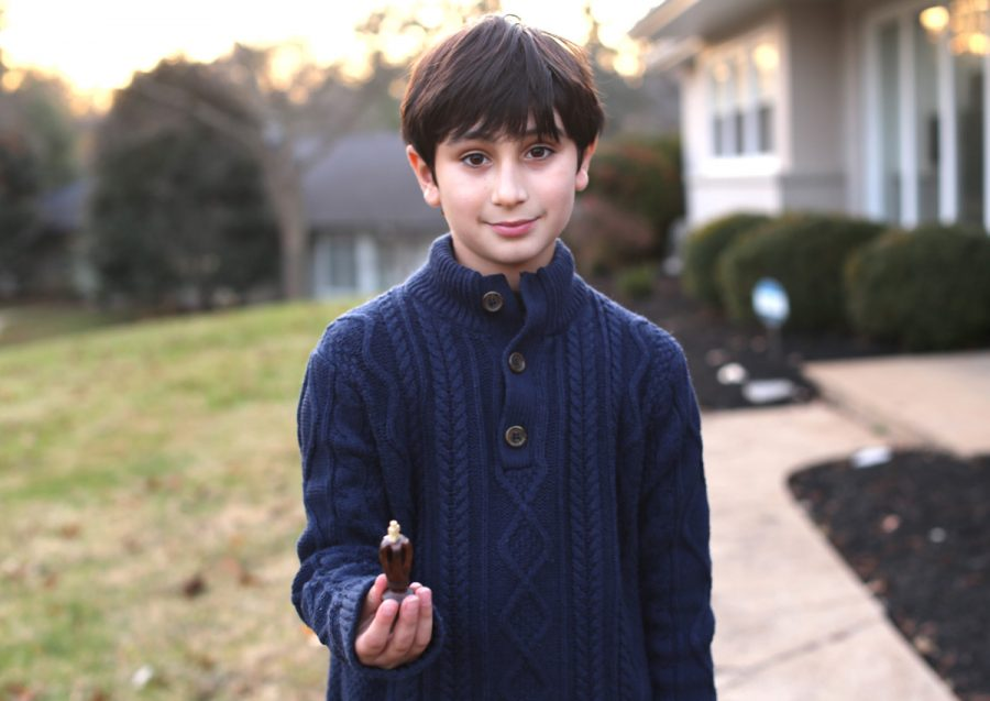 Edan Shoghi holds a black king, his favorite chess piece. He said he considers the king the most valuable attacking piece on the chess board.Photo: Bill Motchan