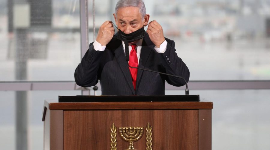 Israeli Prime Minister Benjamin Netanyahu, seen here at a ceremony at Ben Gurion airport on Nov. 26, 2020, said he wants to be the first Israeli to receive a COVID-19 vaccine. (EMIL SALMAN/POOL/AFP via Getty Images)