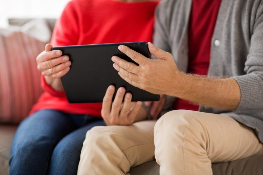 close up of senior couple with tablet pc at home