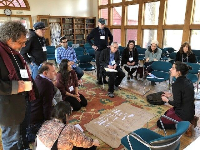 """Mati Esther Engel, bottom right, a performance artist, ritualist and spiritual care practitioner, speaks to participants at a gathering of Kenissa, a network of Jewish """"communities of meaning,"""" held in March 2020 in Falls Village, Conn. (Courtesy of Kenissa)"""