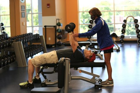 Cathleen Kronemer, a longtime fitness instructor and trainer at the Jewish Community Center, works with a member shortly after the J reopened in June.