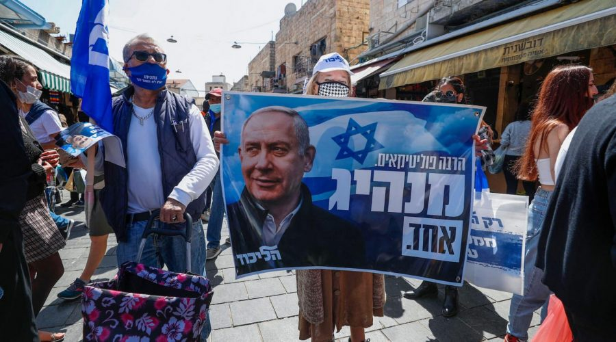 Supporters of Israel's Likud party lift a banner depicting Prime Minister Benjamin Netanyahu during the election campaign at Mahane Yehuda market in Jerusalem, March 19, 2021. (Emmanuel Dunand/AFP via Getty Images)