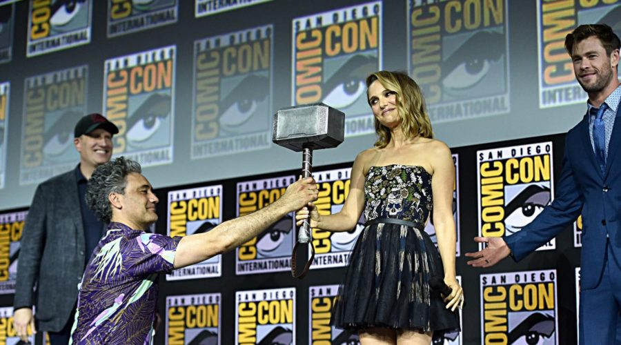 Director Taika Waititi hands Natalie Portman the Thor hammer, as the current Thor star Chris Hemsworth looks on at the San Diego Comic-Con International festival, July 20, 2019. Photo: Alberto E. Rodriguez/Getty Images for Disney