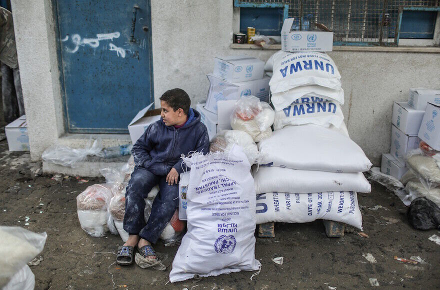 A boy sits near sacks of flour distributed by the United Nations Relief and Works Agency for Palestine Refugees in the Near East at a Gaza refugee camp, Jan. 15, 2018. (Ali Jadallah/Anadolu Agency/Getty Images)
