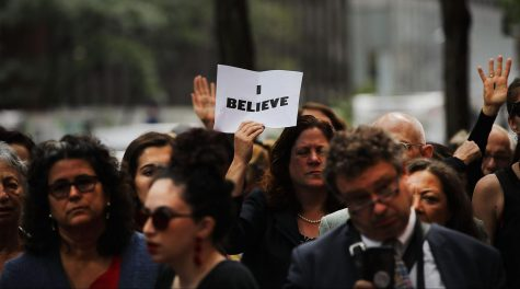 "A sign reads ""I Believe"" at a #MeToo gathering."