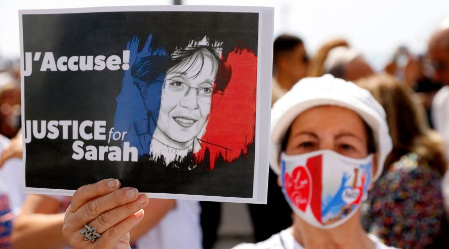 A woman holds up a sign during the day of rallies around the world protesting the French judicial system's handling of the Sarah Halimi case, April 25, 2021. (Jack Guez/AFP/Getty Images)