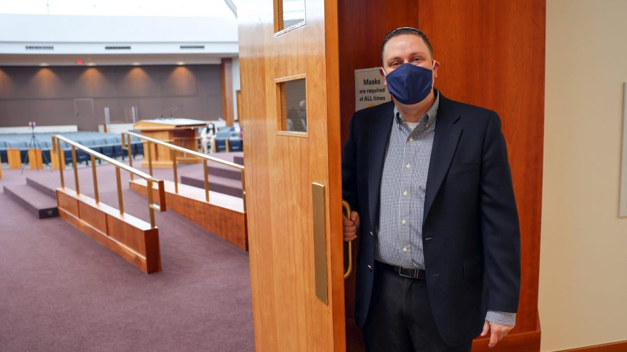 Rabbi Jeffrey Abraham holds open the door to the sanctuary at Congregation B'nai Amoona, which has been holding services at limited capacity since October. Photo: Bill Motchan