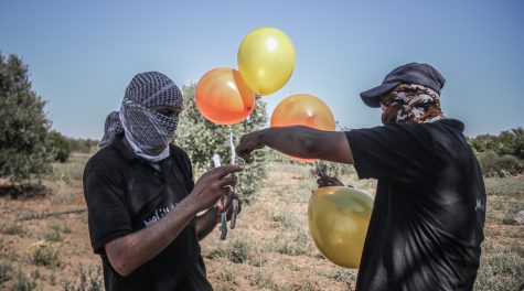 Men prepare incendiary balloons near Gaza city to launch across the border fence towards Israel, June 16, 2021. (Fatima Shbair/Getty Images)