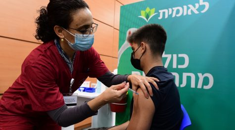 An Israeli student receives a COVID-19 vaccine injection at a vaccination center in Tel Aviv, Jan. 23, 2021. (Avshalom Sassoni/Flash90)