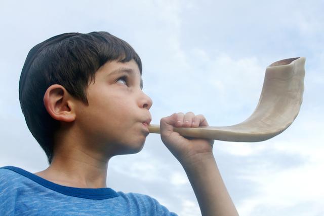 Boy blowing a shofar for Rosh Hashana