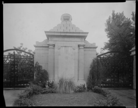 A close-up of the entrance gate at Chesed Shel Emeth Cemetery, located at 7570 Olive. There is a stone structure with two columns in between the two metal gate doors.