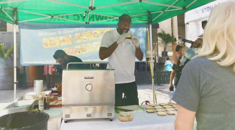 Amare Stoudemire, assistant coach of the Brooklyn Nets, samples one of his own signature Stoudemire Farms burgers at his booth at the Union Square Greenmarket in Manhattan, Oct. 15, 2021. (Julia Gergely)