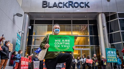 A demonstrator kneels in front of the headquarters of BlackRock in Manhattan, demanding the investment firms  CEO Larry Fink defund the fossil fuel industry, Oct. 18, 2021. (Erik McGregor)